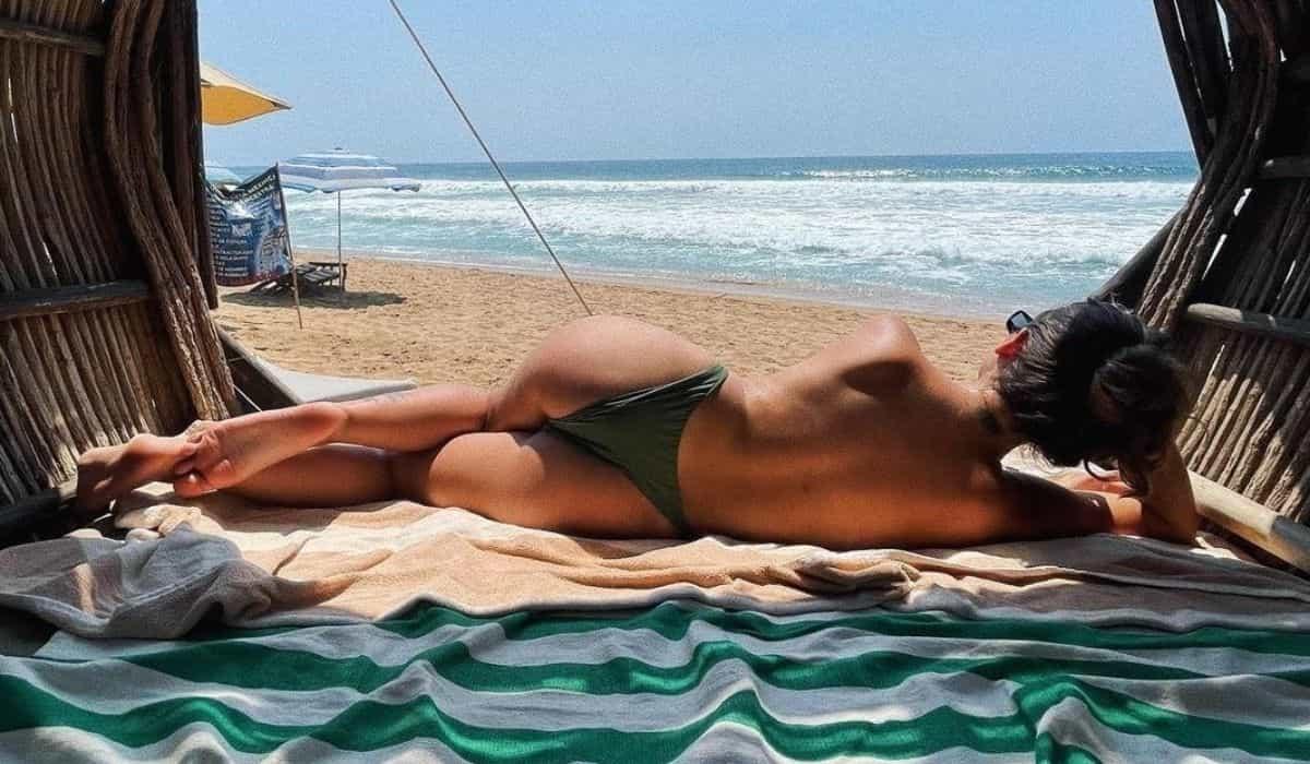 Giovanna Grigio posa fazendo topless em praia durante viagem no México
